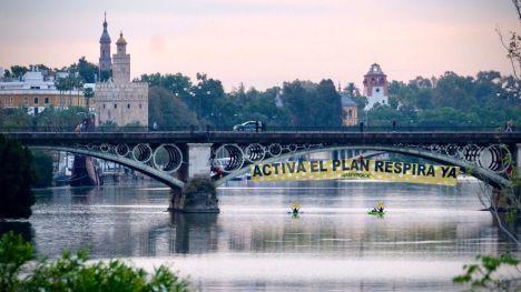 'REinventa Sevilla': Escaladores de Greenpeace se descuelgan con una pancarta en el puente de Triana